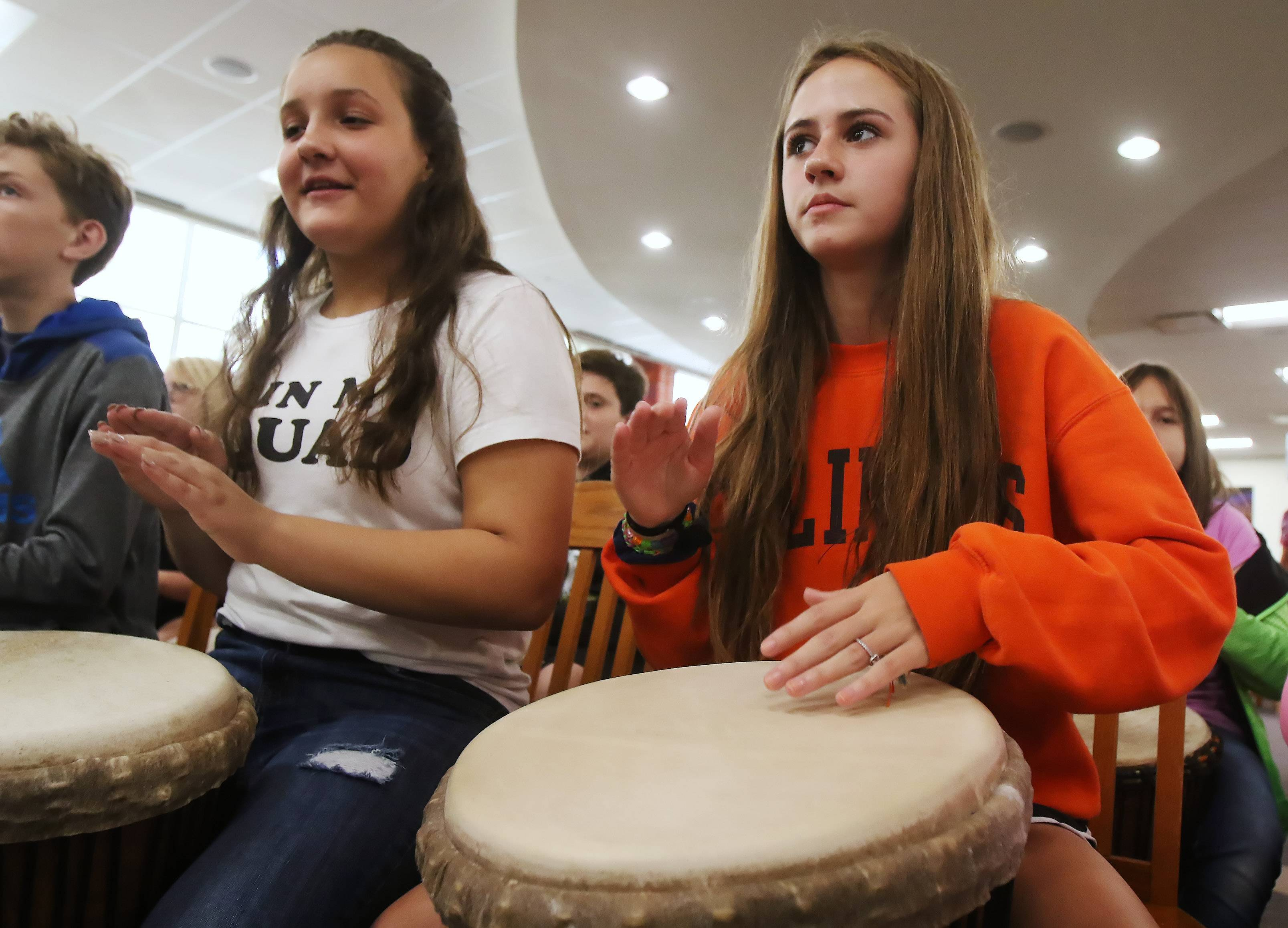 Nicole Stefaniak, right, and Ana Zivkov play djembe drums as students learned to play African drums Thursday at Highland Middle School in Libertyville.