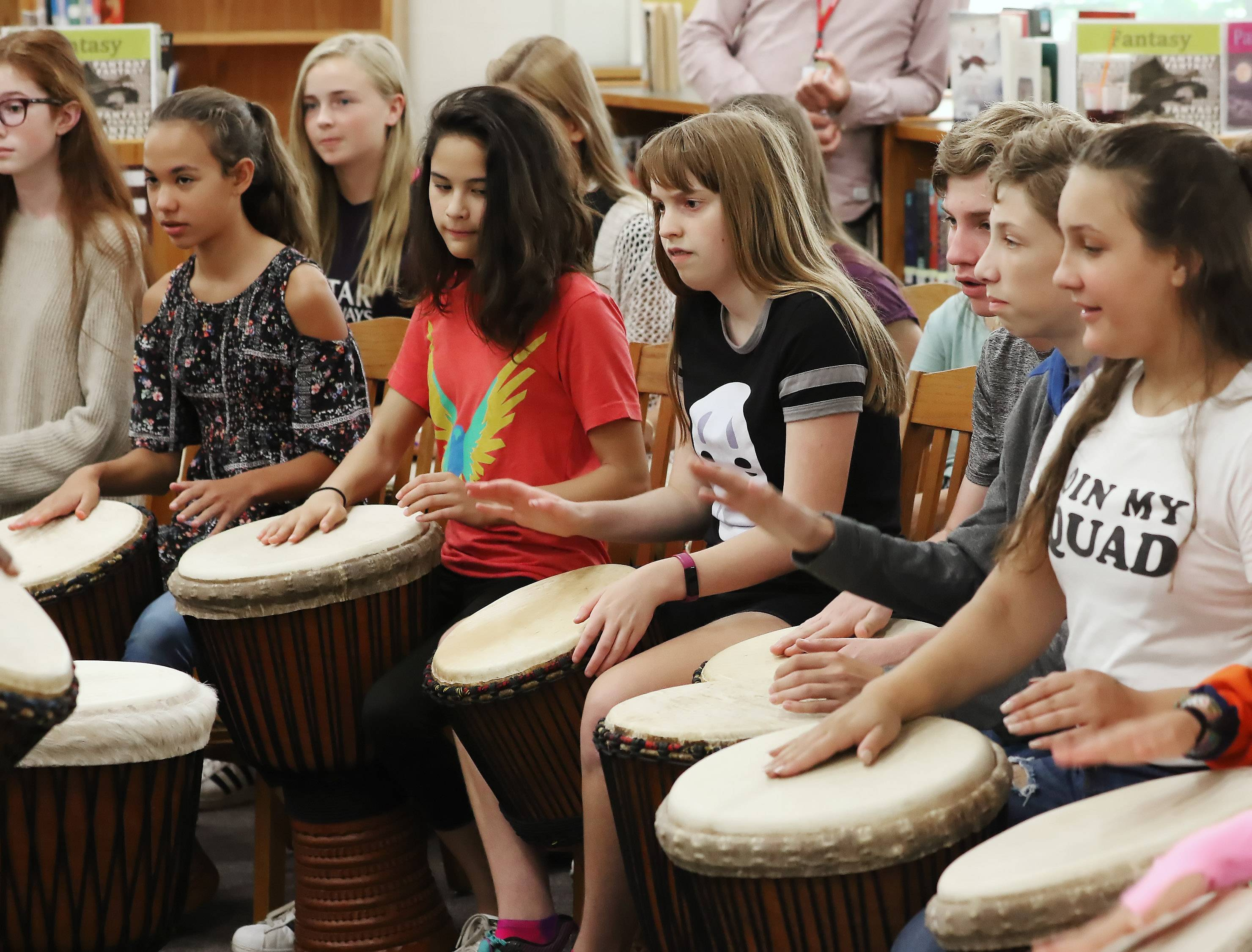 Students learn to play the djembe drums Thursday at Highland Middle School in Libertyville. West African musician Fode Camara and Helen Bond of the Benkadi Project provided instruction on the drums as part of a cultural learning experience.