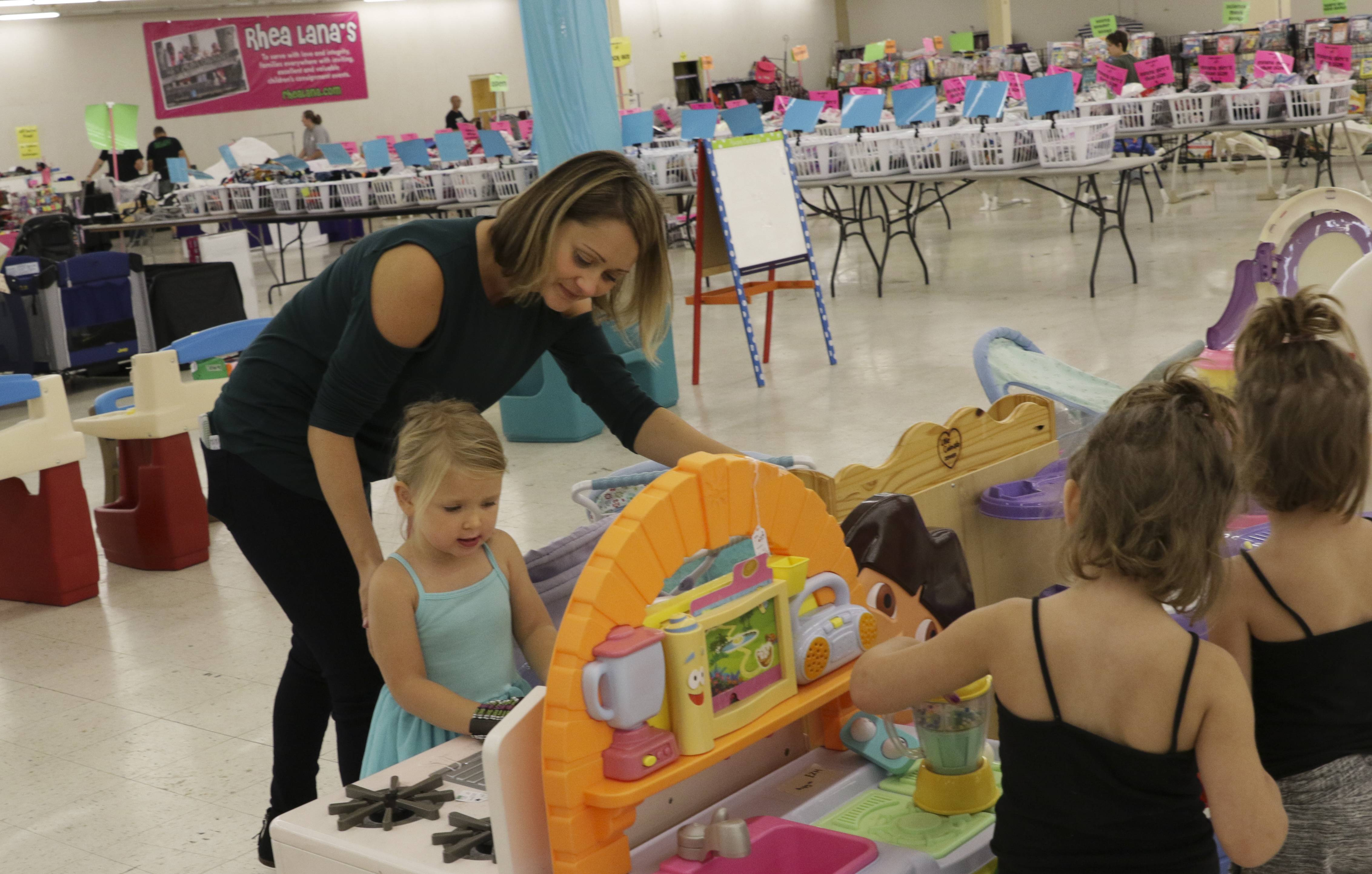 Kelly Frazier of Villa Park helps her daughter Evelyn, 3, as they shop Thursday morning at Rhea Lana's of West Chicagoland in Lombard. The store is a pop-up kids' consignment sale that moved from Naperville to Lombard and wraps up Friday and Saturday with half-price sales.