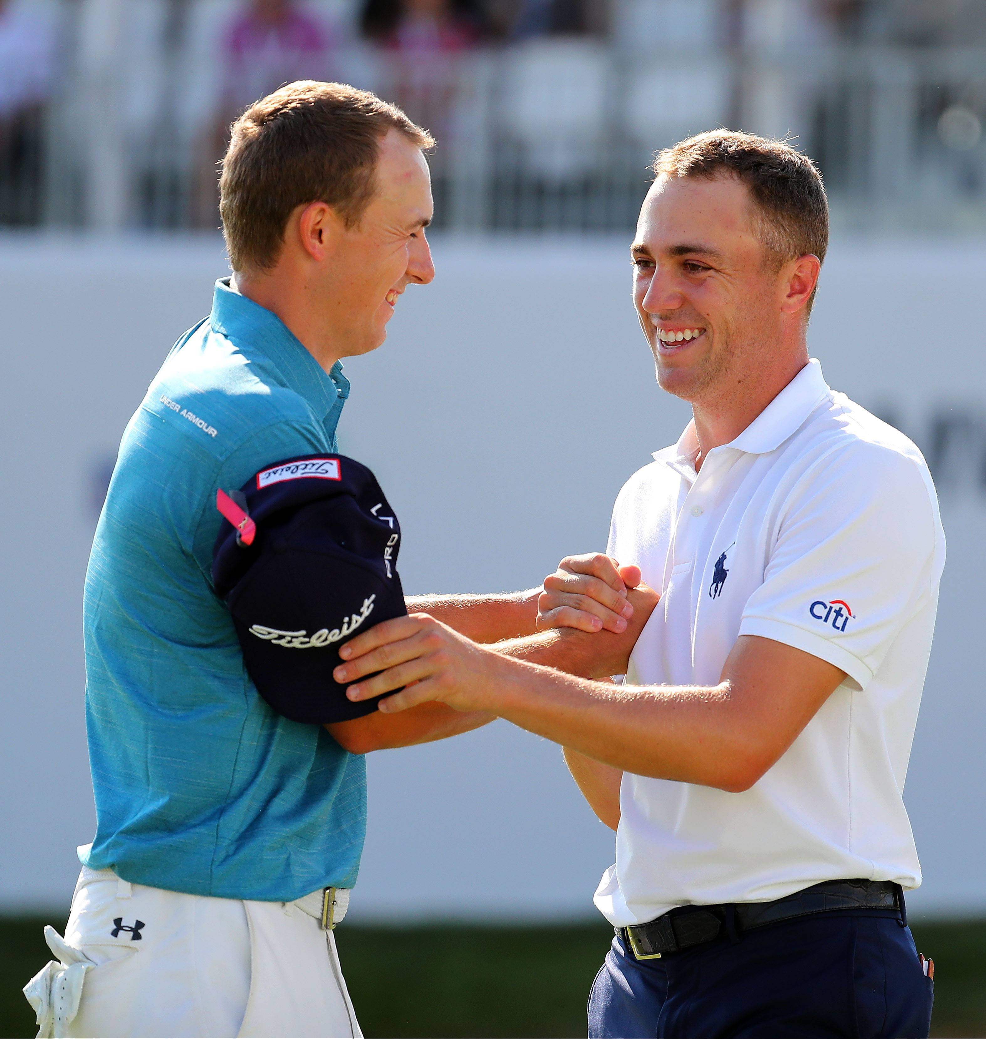 Jordan Spieth, left, and Justin Thomas shake hands on the 18th hole.