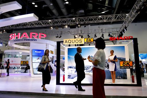 In this Thursday, Sept. 7, 2017, photo, visitors walk by Foxconn's exhibition booth promoting its Sharp 8K flat screen TV in Beijing. The Wisconsin Senate approved nearly $3 billion in cash payments for Foxconn Technology Group on Tuesday, Sept. 12, 2017 while also giving the Taiwanese company a slightly less expedited path to the state Supreme Court for certain legal challenges related to a planned massive electronics manufacturing factory.