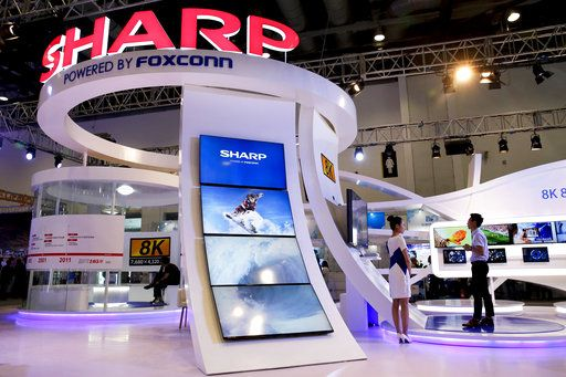 In this Thursday, Sept. 7, 2017, photo, a man plays a video game at Foxconn's exhibition booth promoting its Sharp 8K flat screen TV in Beijing. The Wisconsin Senate approved nearly $3 billion in cash payments for Foxconn Technology Group on Tuesday, Sept. 12, 2017 while also giving the Taiwanese company a slightly less expedited path to the state Supreme Court for certain legal challenges related to a planned massive electronics manufacturing factory.