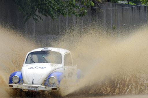 A taxi speeds along a rain flooded street in Acapulco, Guerrero state, Mexico, Thursday, Sept.14, 2017. Hurricane Max hit Mexico's southern Pacific coast as a Category 1 storm Thursday, and was expected to move inland into Guerrero state, a region that includes the resort city of Acapulco. (AP Photo/Bernandino Hernandez)