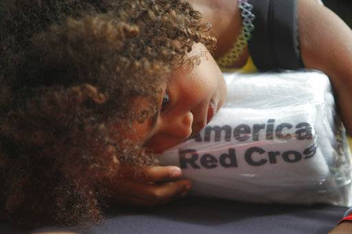 A girl rests her head on a set of towels supplied by the American Red Cross at a makeshift shelter, after arriving in San Juan, Puerto Rico, Thursday, Sept. 14, 2017, on a cruise ship with families evacuated from Caribbean islands devastated by Hurricane Irma. Puerto Rico transformed their largest convention center into a shelter for some of the hurricane victims. Some of those arriving via the cruise ship said they would stay with friends and family in the U.S. mainland until they got a better idea on how long reconstruction would take. (AP Photo/Ricardo Arduengo)