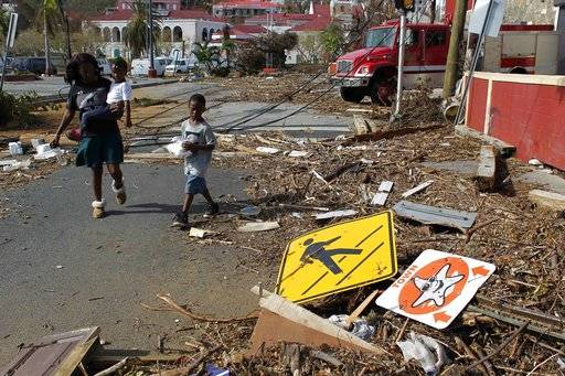 A woman with her two children walk past debris left by Hurricane Irma in Charlotte Amalie, St. Thomas, U.S. Virgin Islands, Sunday, Sept. 10, 2017.  The storm ravaged such lush resort islands as St. Martin, St. Barts, St. Thomas, Barbuda and Anguilla.