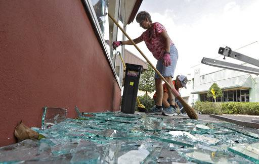 Building owner Catharine Taylor Woods, front, and Jessica Newman, of the City of Wauchula clean up broke glass after an awning blew off in Hurricane Irma and broke several windows early Monday, Sept. 11, 2017, in Wauchula, Fla.