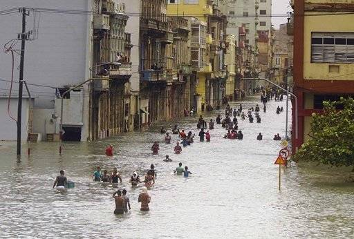People move through flooded streets in Havana after the passage of Hurricane Irma, in Cuba, Sunday, Sept. 10, 2017. The powerful storm ripped roofs off houses, collapsed buildings and flooded hundreds of miles of coastline after cutting a trail of destruction across the Caribbean. Cuban officials warned residents to watch for even more flooding over the next few days.