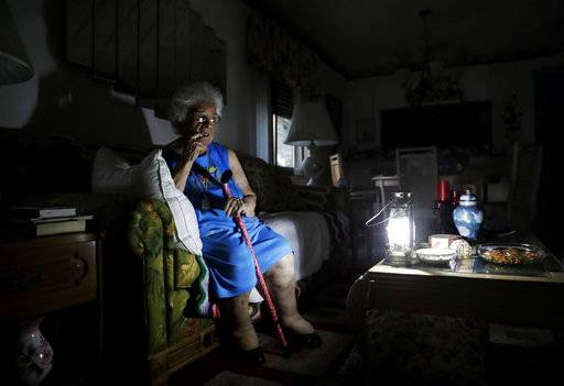 "Mary Della Ratta, 94, sits by a battery powered lantern in her home three days after Hurricane Irma knocked out power in Naples, Fla., Wednesday, Sept. 13, 2017. ""I don't know what to do. How am I going to last here?"" said Della Ratta. The number of people without electricity in the steamy late-summer heat was down to 6.8 million. Utility officials warned it could take over a week for power to be fully restored."