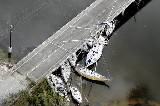 Boats are wedged under a bridge in Marathon, Fla., in the aftermath of Hurricane Irma, Wednesday, Sept. 13, 2017. Irma laid waste to beautiful Caribbean islands and caused historic destruction across Florida. The cleanup will take weeks; recovery will take months. (Mike Stocker/South Florida Sun-Sentinel via AP)