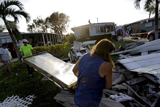 Joseph Ross, left, cleans up debris from his damaged home with help from a neighbor in the aftermath of Hurricane Irma in Naples, Fla., Wednesday, Sept. 13, 2017.