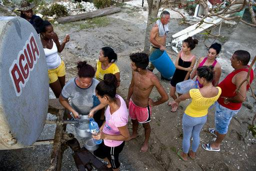 Locals affected by Hurricane Irma line up to collect drinking water in Isabela de Sagua, Cuba, Monday, Sept. 11, 2017. The powerful storm ripped roofs off houses, collapsed buildings and flooded hundreds of thousands of coastline after cutting a trail of destruction across the Caribbean. Cuban officials warned residents to watch for even more flooding over the next few days.