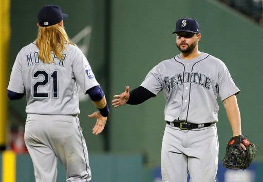 Seattle Mariners' Taylor Motter (21) and Yonder Alonso, right, congratulate each other on the team's 10-4 win over the Texas Rangers in a baseball game, Thursday, Sept. 14, 2017, in Arlington, Texas. (AP Photo/Tony Gutierrez)