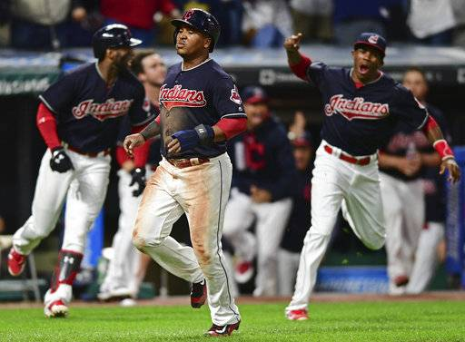 Cleveland Indians' Jose Ramirez, front, scores on a double by Jay Bruce during the 10th inning of a baseball game against the Kansas City Royals, Thursday, Sept. 14, 2017, in Cleveland. The Indians won 3-2. (AP Photo/David Dermer)