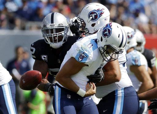 Tennessee Titans quarterback Marcus Mariota (8) fumbles the ball as he is hit by Oakland Raiders defensive end Khalil Mack (52) in the second half of an NFL football game Sunday, Sept. 10, 2017, in Nashville, Tenn. The Titans recovered the ball. (AP Photo/James Kenney)