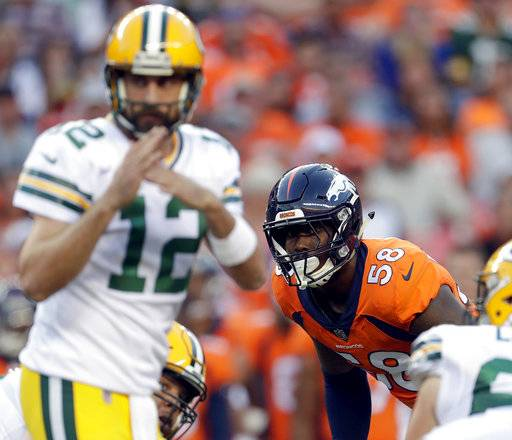 "FILE - In this Aug. 26, 2017, file photo, Denver Broncos outside linebacker Von Miller (58) watches as Green Bay Packers quarterback Aaron Rodgers (12) calls time out during the first half of an NFL preseason football game in Denver. Von Miller can't wait to bust out some of his new sack dances like the ""Sexy T-Rex"" he introduced after dumping Aaron Rodgers in the preseason. Trouble is, Miller has now gone without a sack for a career-long five consecutive regular season games. (AP Photo/Joe Mahoney, File)"