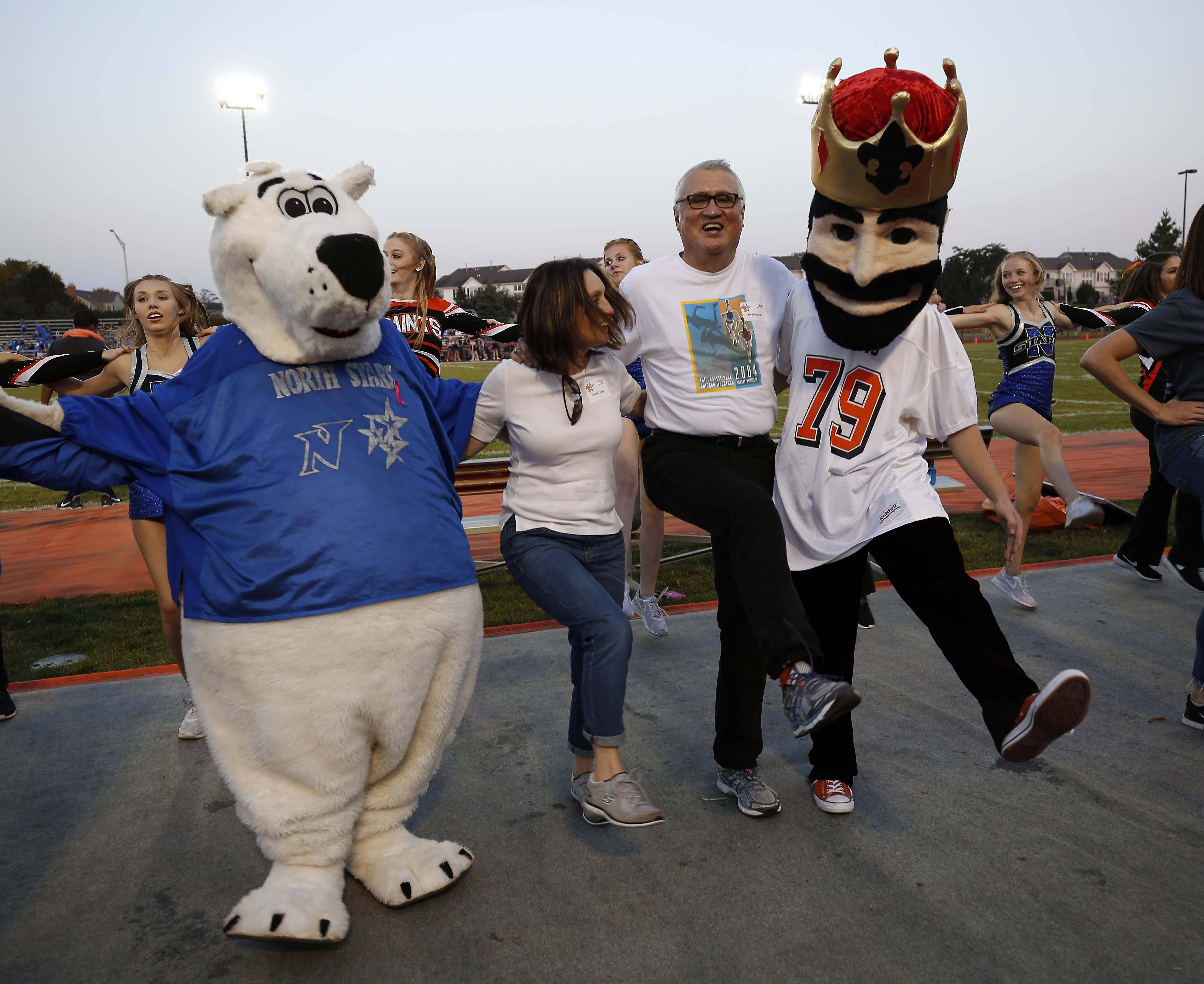 Brian Hill/bhill@dailyherald.com St. Charles Mayor Ray Rogina and Diane Cullen are sandwiched between the East and North mascots Friday during the annual Kick-A-Thon for St. Charles East and North high schools to raise money for cancer research.