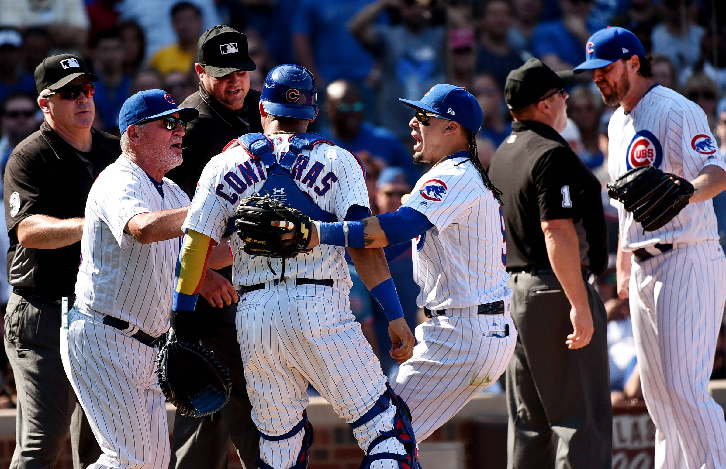 Chicago Cubs catcher Willson Contreras (40) is restrained by Chicago Cubs manager Joe Maddon (70) and Chicago Cubs second baseman Javier Baez (9) after being ejected by umpire Jordan Baker (71) in the 5th inning during St. Louis Cardinals at Chicago Cubs.