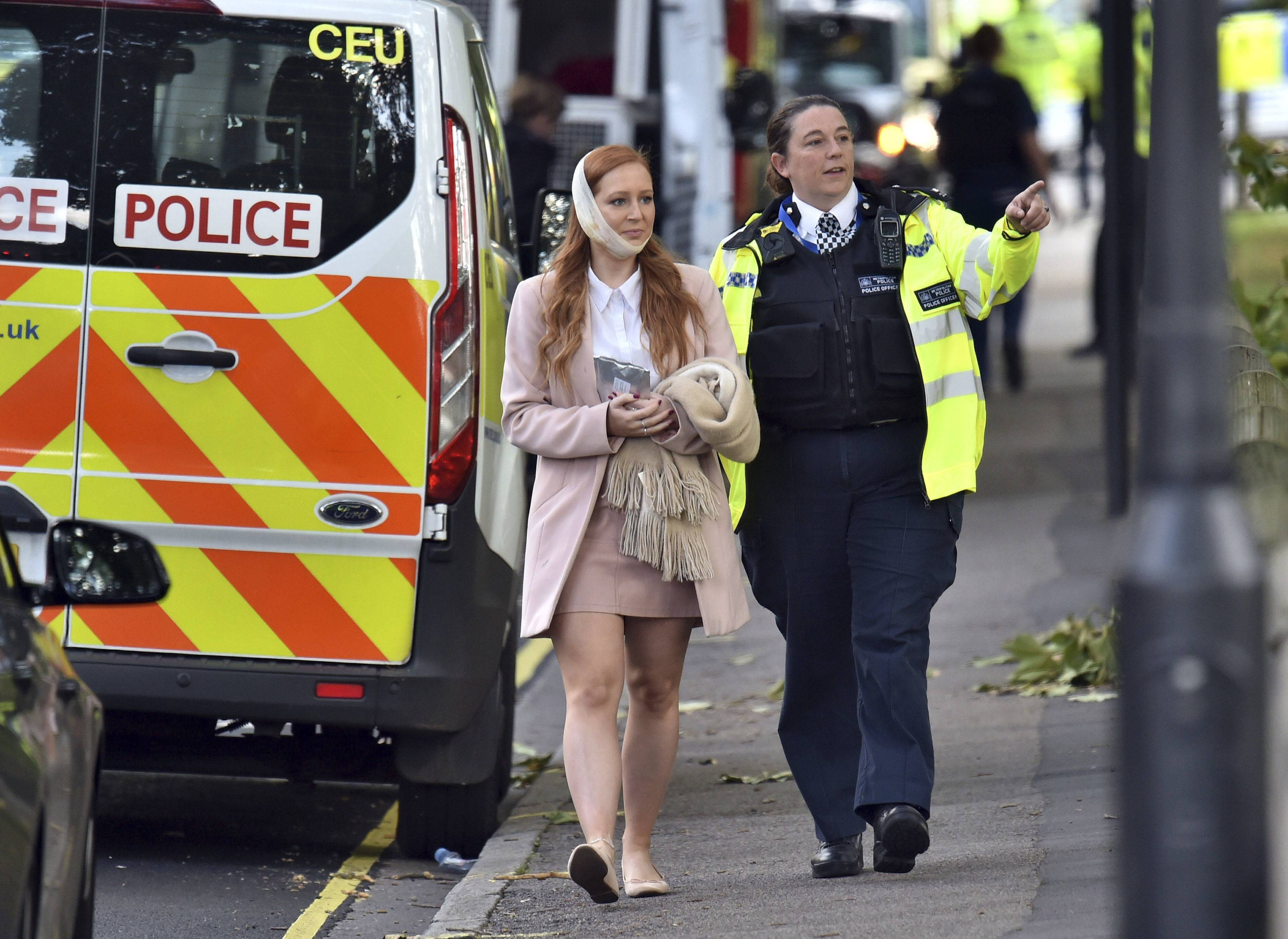 "An injured woman is assisted by a police officer close to Parsons Green station Friday in west London after an explosion on a packed London Underground train. London's Metropolitan Police says a fire on the London subway has been declared a ""terrorist incident."""