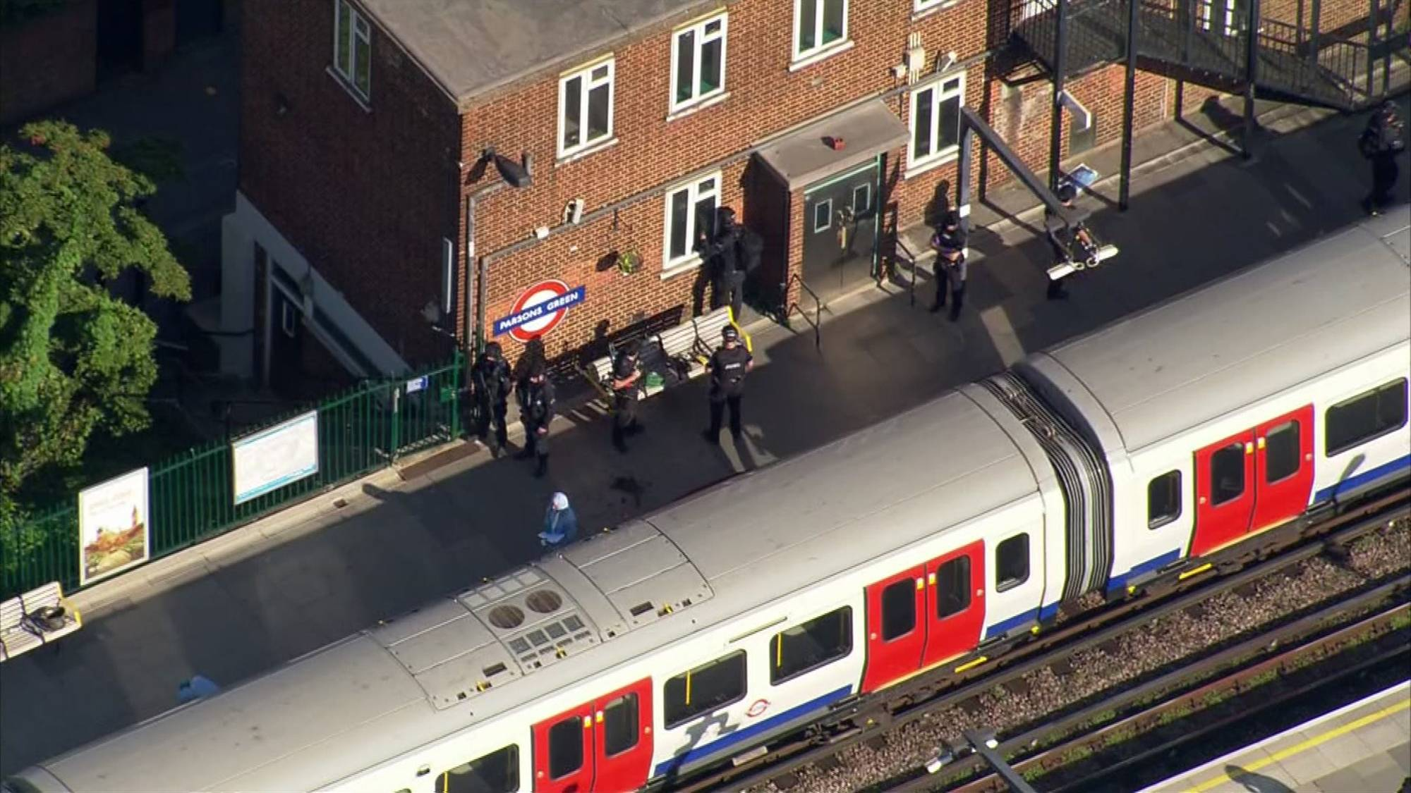 In this aerial image made from video, police officers work at the Parsons Green Underground Station after an explosion in London Friday, Sept. 15, 2017. A reported explosion at a train station sent commuters stampeding in panic, injuring several people at the height of London's morning rush hour, and police said they were investigating it as a terrorist attack. (Pool via AP)