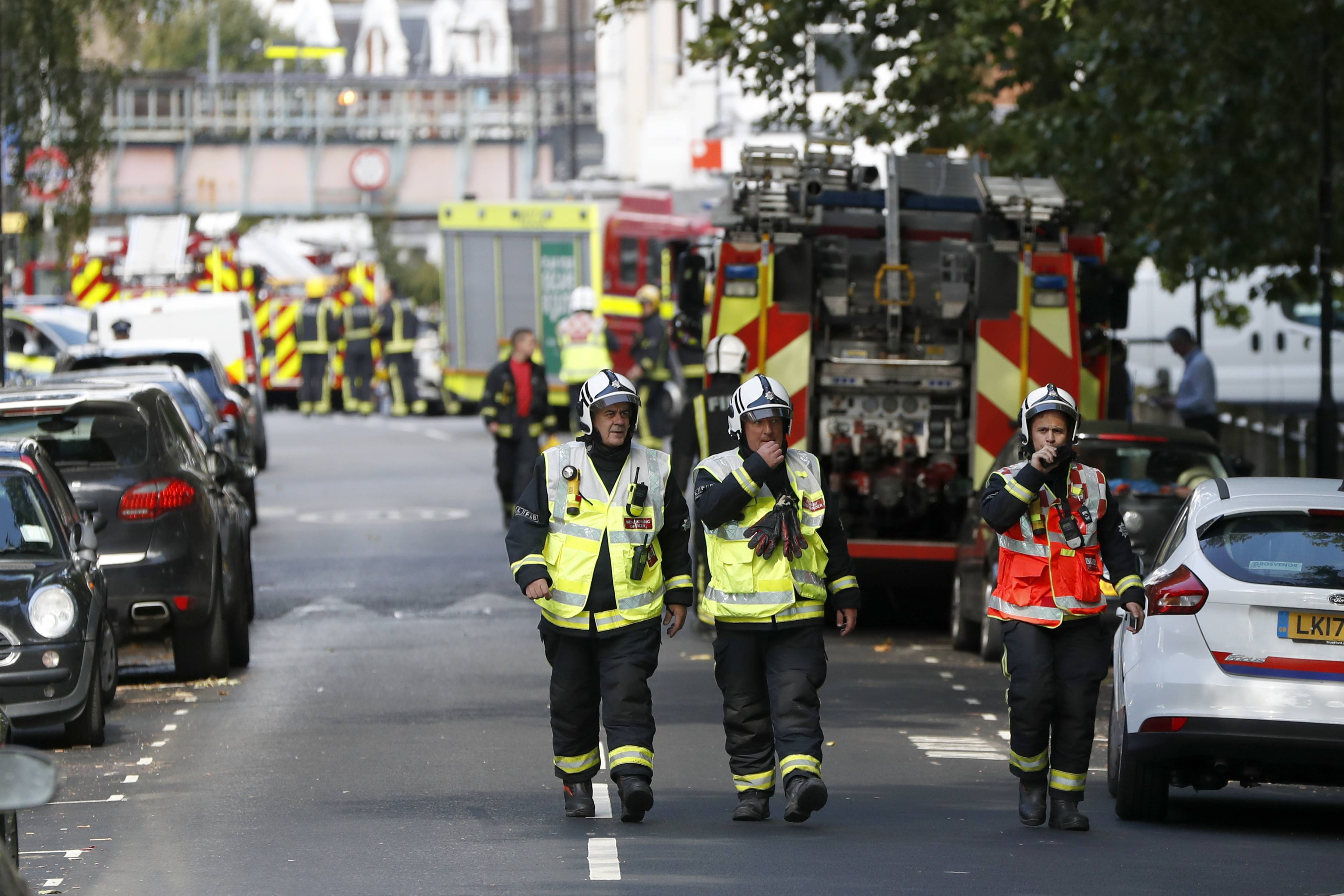 Fire brigade officers walk within a cordon near where an incident happened, that police say they are investigating as a terrorist attack, at Parsons Green subway station in London, Friday, Sept. 15, 2017. A bucket wrapped in an insulated bag caught fire on a packed London subway train Friday, sending commuters stampeding in panic at the height of the morning rush hour.