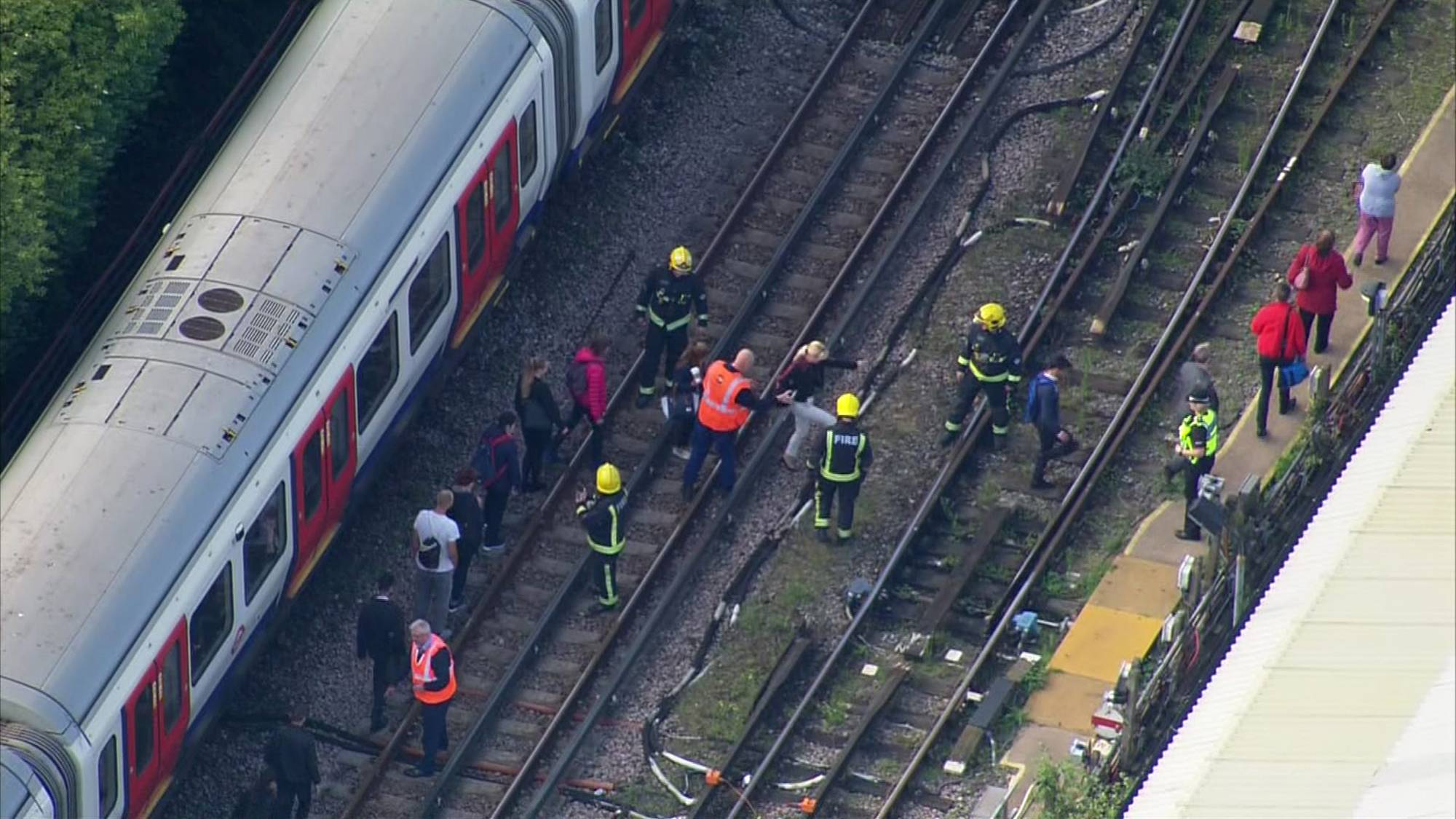 In this aerial image made from video, emergency workers help people to disembark a train near the Parsons Green Underground Station after an explosion in London Friday, Sept. 15, 2017. A reported explosion at a train station sent commuters stampeding in panic, injuring several people at the height of London's morning rush hour, and police said they were investigating it as a terrorist attack. (Pool via AP)