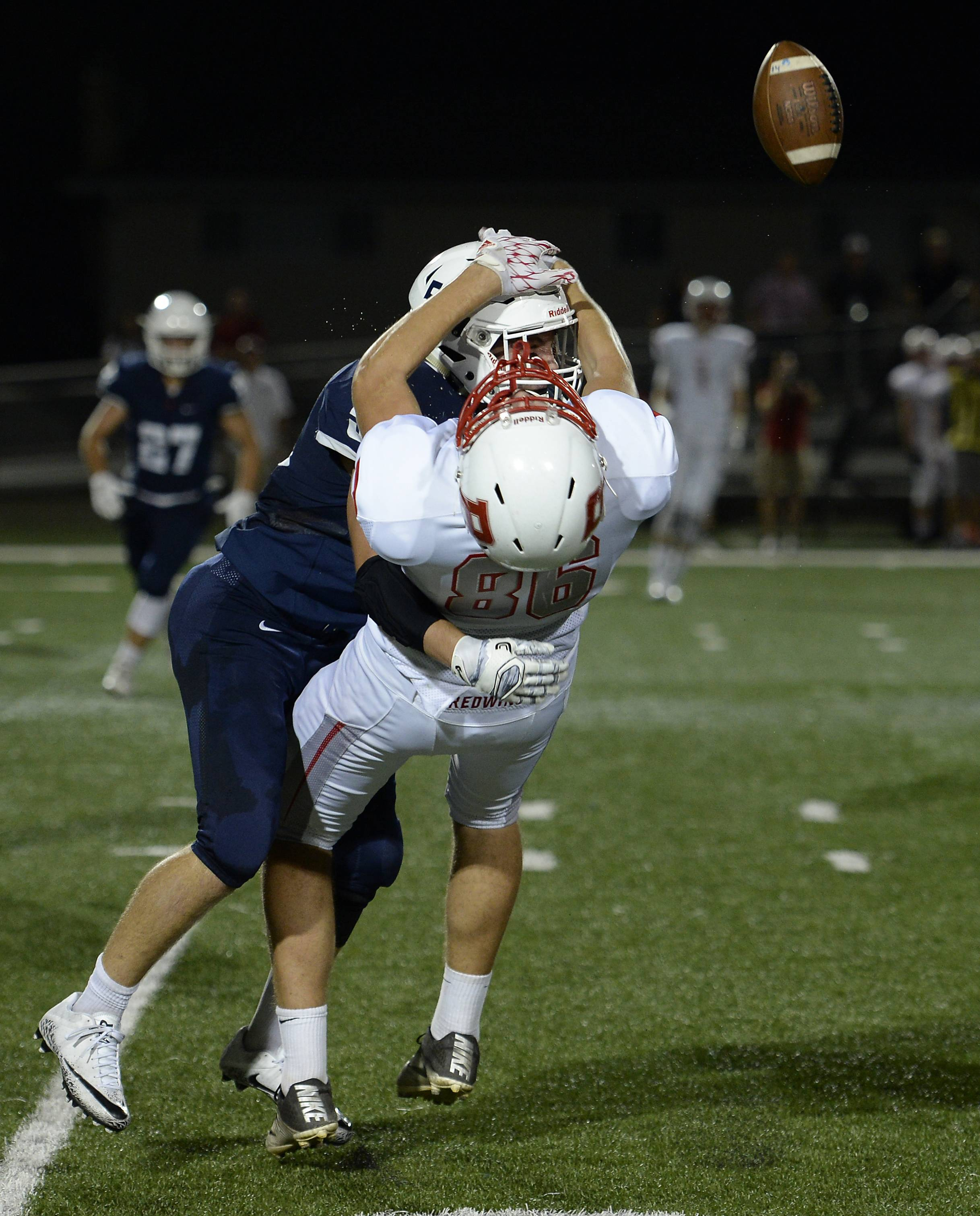 St. Viator's Jake Wolf lays out Benet Academy's Anthony Adams on a pass play during the first half of varsity football on Friday.