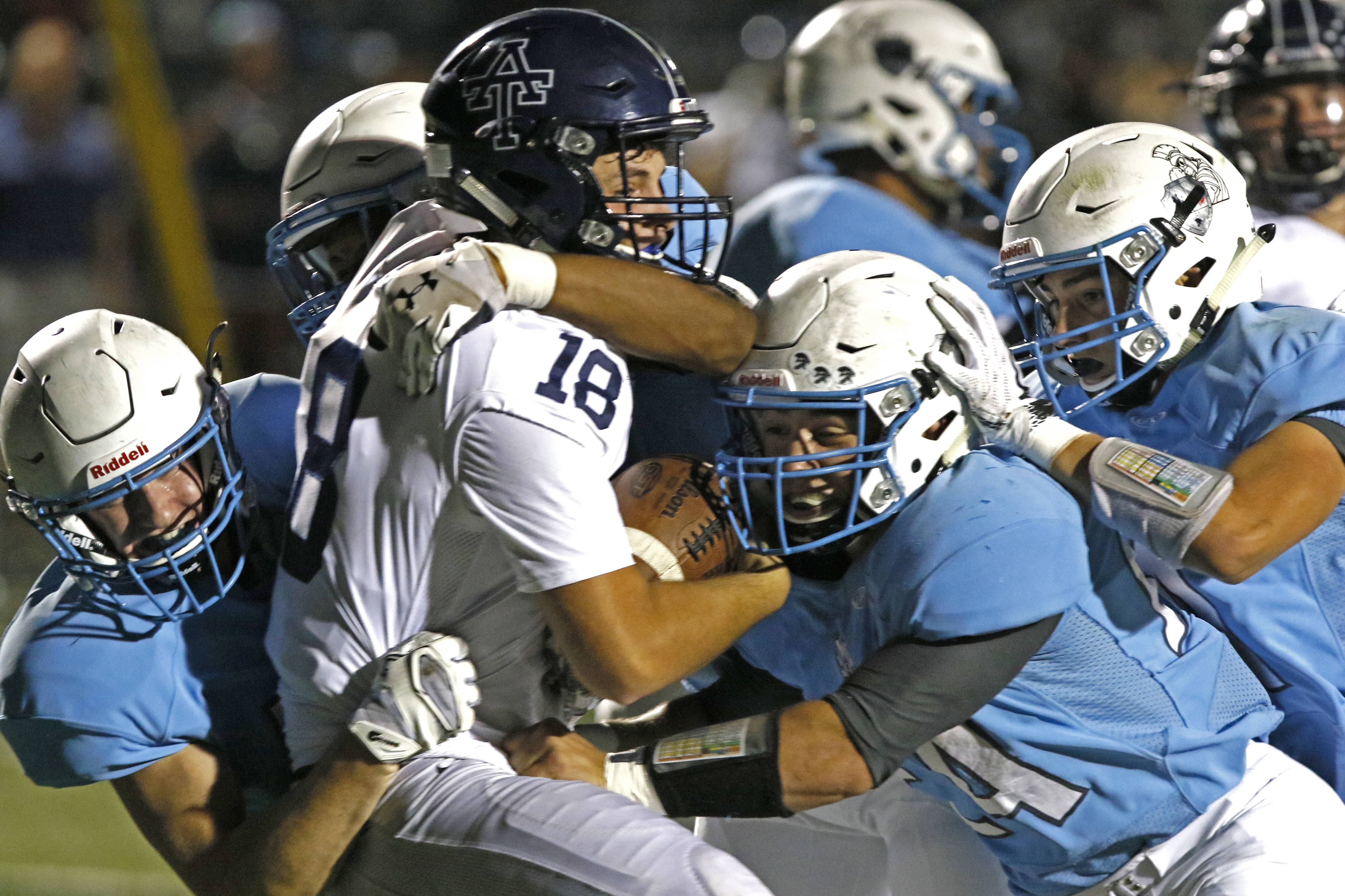 Addison Trail quarterback Nick Daudelin (18) is sacked near his endzone by four Wiilowbrook Warriors led by Jack Jessen, right, early in the first quarter, September 15, 2017, in Villa Park.