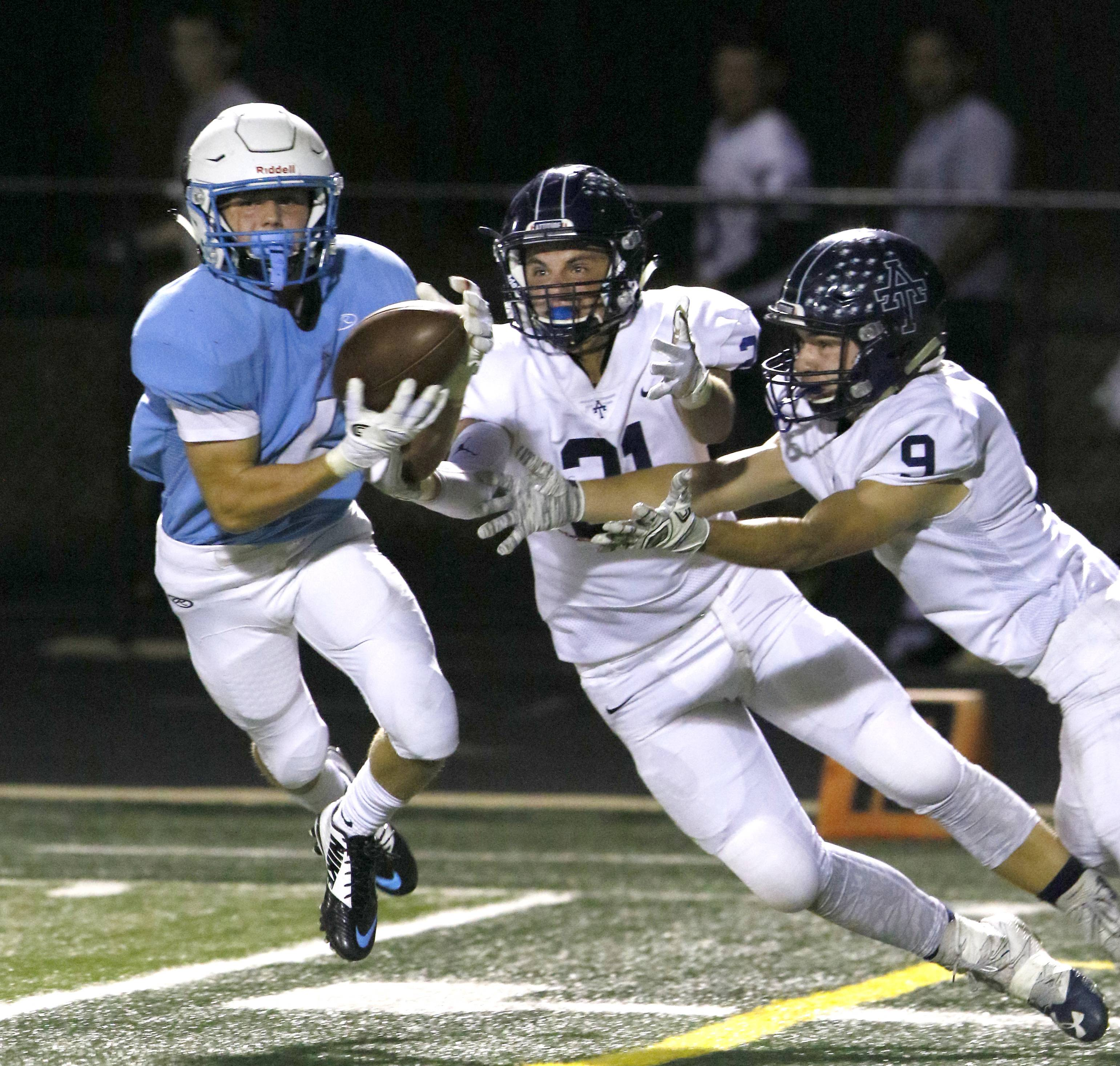 Willowbrook High School's Sam Tumilty, left, steps in front of Addison Trail's Vince Daudelin (21) and Dennis Ionikov (9) to intercept the ball and run for a 90-yard touchdown during first half action, September 15, 2017, in Villa Park.