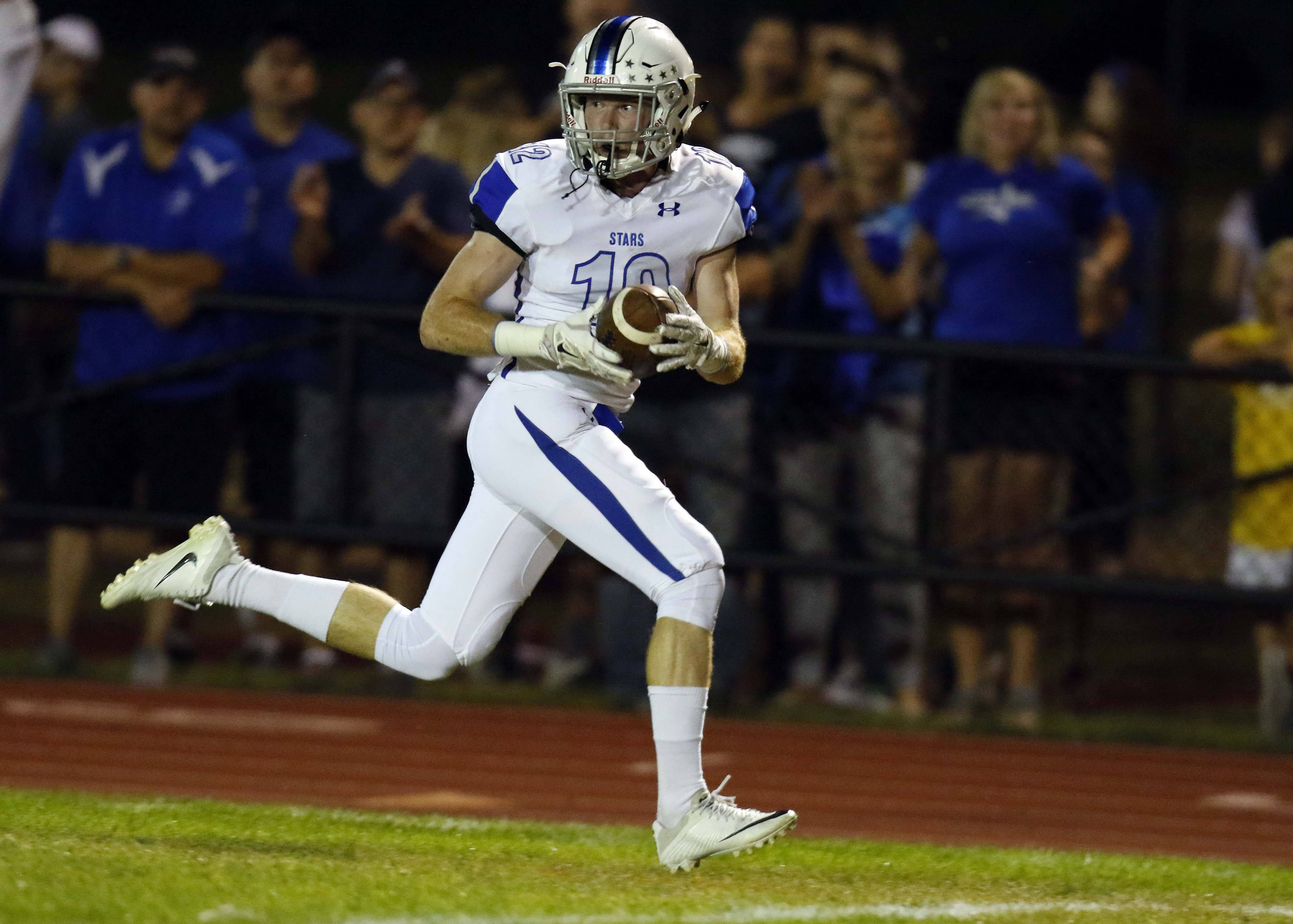 St. Charles North's Thomas Nelsen (12) heads to the end zone for a touchdown.