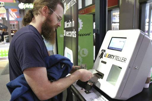 FILE - In this Monday, March 31, 2014, file photo, Tim McCormack, of Boston, inserts cash into a Liberty Teller ATM while purchasing bitcoins at South Station train station, in Boston. On Thursday, Sept. 14, 2017, Bitcoin tumbled 15 percent to about $3,300 against the dollar. (AP Photo/Steven Senne, File)