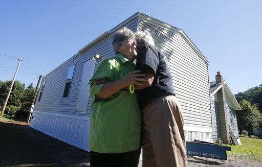 "FILE - In this Aug. 23, 2016, file photo, Mayor Andrea ""Andy"" Pendleton, right, hugs resident Linda Bennett in front of Bennett's new FEMA trailer installed in front of her flood ravaged home in Rainelle, W. Va. Just before Hurricane Harvey made landfall in Texas in August 2017 as a Category 4 hurricane and in the floods that ensued, the federal government was auctioning off used disaster-response trailers at fire-sale prices. (AP Photo/Steve Helber, File)"