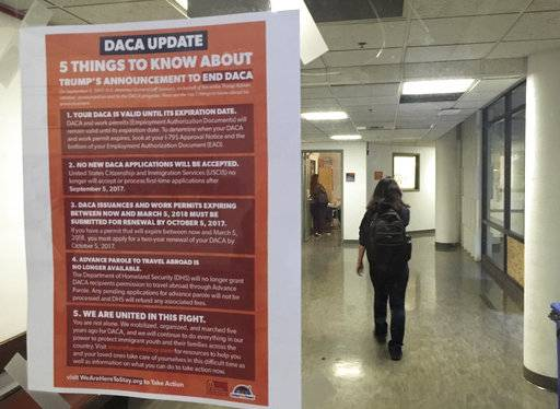 "In this photo taken Sept. 7, 2017, a student walks past a tip sheet for Deferred Action for Childhood Arrivals recipients who fear deportation that is taped to a window on the University of California, Berkeley campus in Berkeley, Calif. Colleges and universities nationwide are stepping up efforts to help the students who are often called ""Dreamers,"" after the Trump administration announced plans last week to end that federal program protecting immigrants brought to the U.S. illegally as children. (AP Photo/Jocelyn Gecker)"