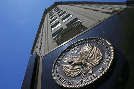 FILE - In this June 21, 2013, file photo, the seal affixed to the front of the Department of Veterans Affairs building in Washington. A new first-of-its kind government study finds suicide among military veterans is especially high in the western U.S. and rural areas. The numbers suggest that social isolation, gun ownership and limited health care access may be factors behind the higher numbers. The Department of Veterans Affairs released data Sept. 15, on suicide by state. (AP Photo/Charles Dharapak, File)