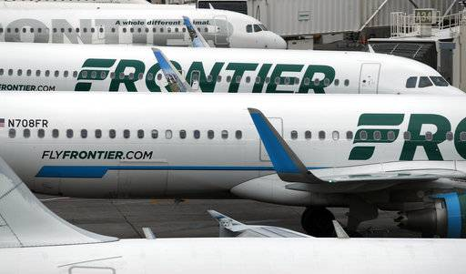 In this Monday, May 15, 2017, photograph, Frontier Airlines jets sit at gates on the A Concourse at Denver International Airport in Denver. The U.S. government has fined Frontier $1.5 million for keeping passengers stuck on a dozen grounded aircraft for more than three hours during a snowstorm at the Denver airport in December 2016. But the federal Department of Transportation said Friday, Sept. 15, 2017, it will forgive $900,000 of that because of compensation the airline says it paid to passengers. (AP Photo/David Zalubowski, File)