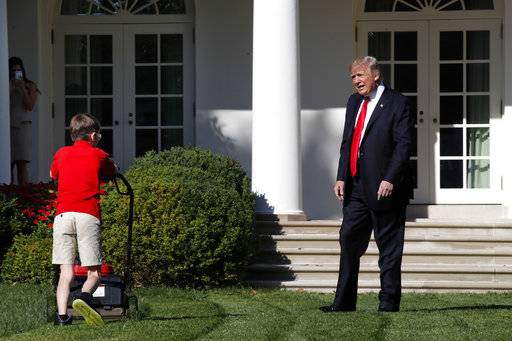Frank Giaccio, 11, of Falls Church, Va., is surprised by President Donald Trump, Friday, Sept. 15, 2017, as he mows the lawn of the Rose Garden at the White House in Washington. The 11-year-old was focused on the job at hand and didn't notice the president until he was right next to him. (AP Photo/Jacquelyn Martin)