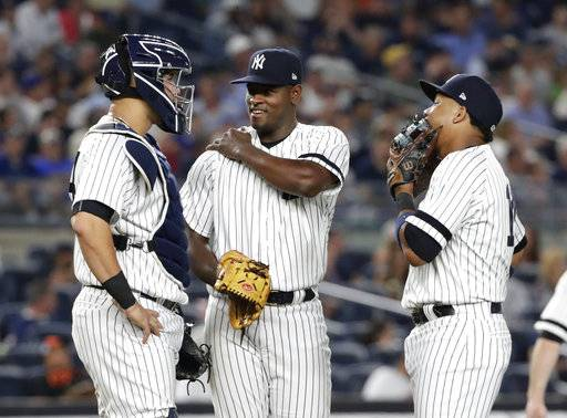 New York Yankees starting pitcher Luis Severino, center, talks with catcher Gary Sanchez, left, and Starlin Castro, right, during the third inning of a baseball game against the Baltimore Orioles Friday, Sept. 15, 2017, in New York. (AP Photo/Frank Franklin II)