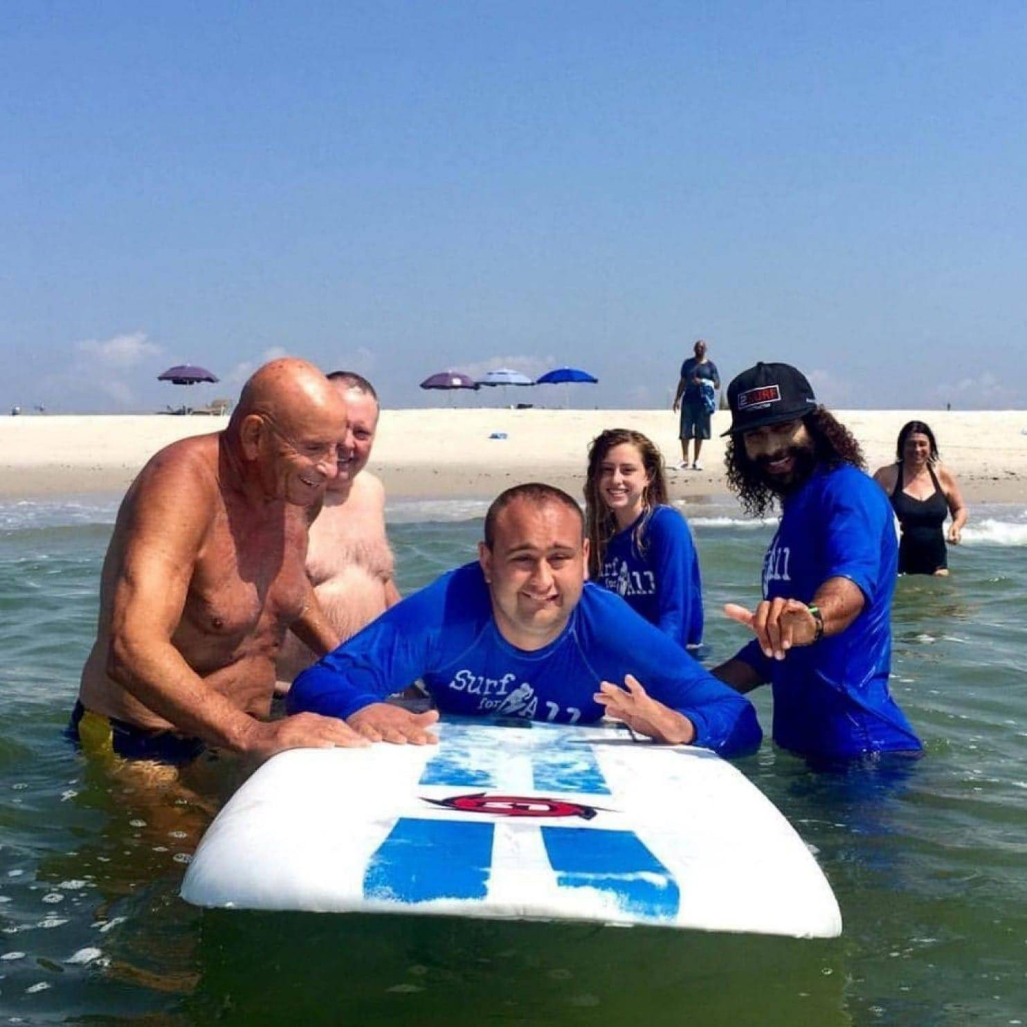 Dan Mulvaney, who suffers from a rare form of autism, has found joy on a surfboard. Surrounding him from left to right are family friend Harvey Weisenberg, his father James Mulvaney and two surf instructors.