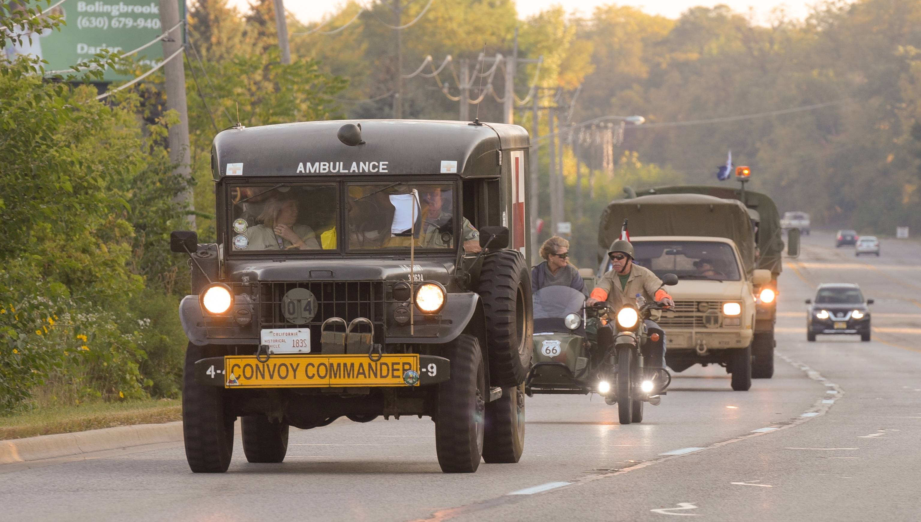In their 1964 Dodge military ambulance, Dan and Janine McCluskey of Simi Valley, California, lead a convoy of vintage military vehicles that left the DuPage County Fairgrounds in Wheaton shortly after dawn Saturday. The group of 60 vehicles will travel on historic U.S. Route 66 to Santa Monica, California.