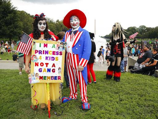 "Theresa Lindsey, left, dressed as Snow White and Timothy Schlarmann, center, dressed as Uncle Sam, both from southern California, join other juggalos, as supporters of the rap group Insane Clown Posse are known, in front of the Lincoln Memorial in Washington during a rally, Saturday, Sept. 16, 2017, to protest and demand that the FBI rescind its classification of the juggalos as ""loosely organized hybrid gang."" (AP Photo/Pablo Martinez Monsivais)"