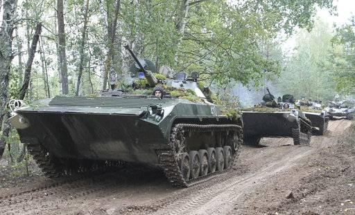 In this photo taken on Friday, Sept. 15, 2017, Belarusian army vehicles drive during the war games at an undisclosed location in Belarus. Russia and Belarus began major war games Thursday, an operation involving thousands of troops, tanks and aircraft on NATO's eastern edge practicing how to hunt down and destroy armed spies, among other maneuvers. (Vayar Military Agency photo via AP)
