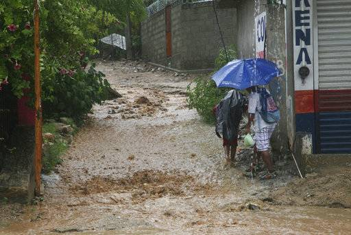 People walk under a downpour on a flooded street in Acapulco, Guerrero state, Mexico, Thursday, Sept. 14, 2017. Hurricane Max hit Mexico's southern Pacific coast as a Category 1 storm Thursday and was expected to move inland into Guerrero state, a region that includes the resort city of Acapulco.(AP Photo/Bernandino Hernandez)