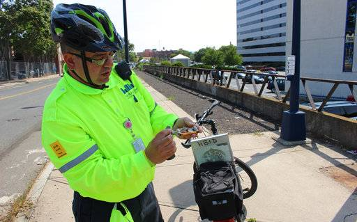 Eddie Zayas, a safety ambassador for the Hartford Business Improvement District, shows off some of his bicycle repair tools during patrol of downtown streets on Sept. 2, 2017. Zayas is part of a program that provides free roadside assistance to bicyclists who break down in Connecticut's capital city (AP Photo/Pat Eaton-Robb)