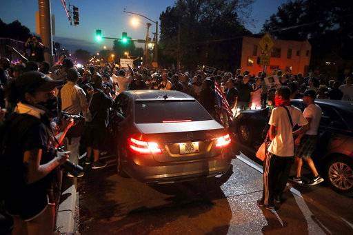 Protesters surround a car as they march in the street response to a not guilty verdict in the trial of former St. Louis police officer Jason Stockley Saturday, Sept. 16, 2017, in St. Louis. Stockley was acquitted in the 2011 killing of a black man following a high-speed chase. After an exchange, the car was allowed to pass. (AP Photo/Jeff Roberson)