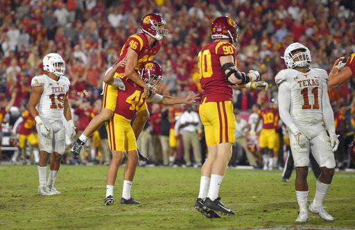 Southern California's Chase McGrath (40) celebrates with holder Wyatt Schmid (46) and linebacker Connor Murphy, second from right, as Texas defensive back Brandon Jones, left, and defensive back P.J. Locke III watch after McGrath kicked a 43-yard field goal to win the game in the second overtime of an NCAA college football game, Saturday, Sept. 16, 2017, in Los Angeles. USC won 27-24. (AP Photo/Mark J. Terrill)