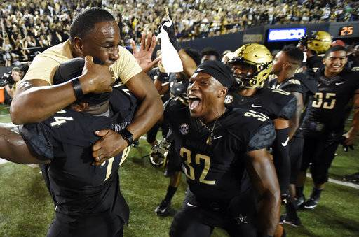 Vanderbilt head coach Derek Mason, top left, celebrates with Jay Woods (74) and Jamauri Wakefield (32) after defeating Kansas State in an NCAA college football game, Saturday, Sept. 16, 2017, in Nashville, Tenn. Vanderbilt Won 14-7. (AP Photo/Mark Zaleski)