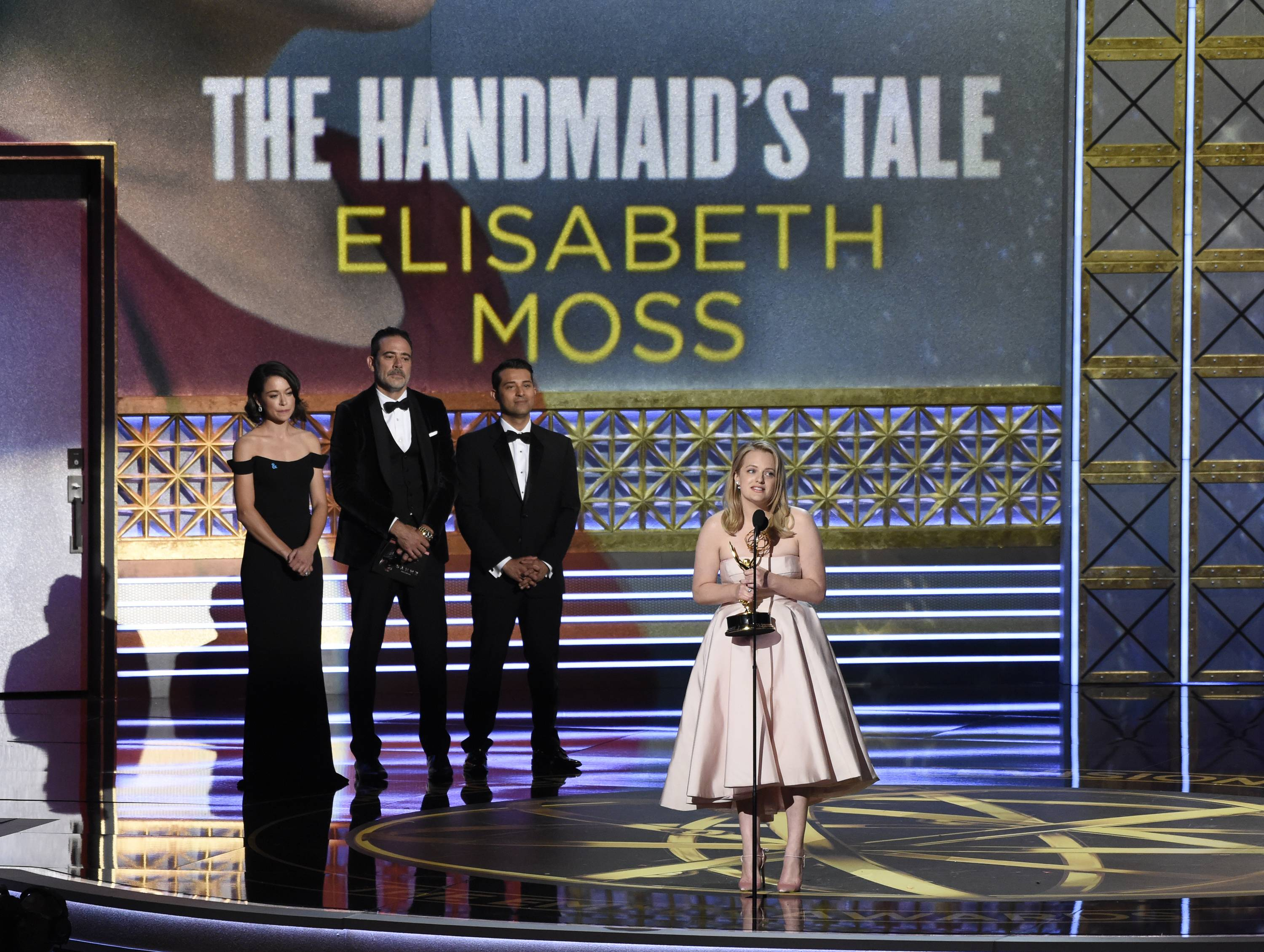 "Elisabeth Moss, center, accepts the award for outstanding lead actress in a drama series for ""The Handmaid's Tale"" while Tatiana Maslany, left, and Jeffrey Dean Morgan look on at the 69th Primetime Emmy Awards on Sunday."