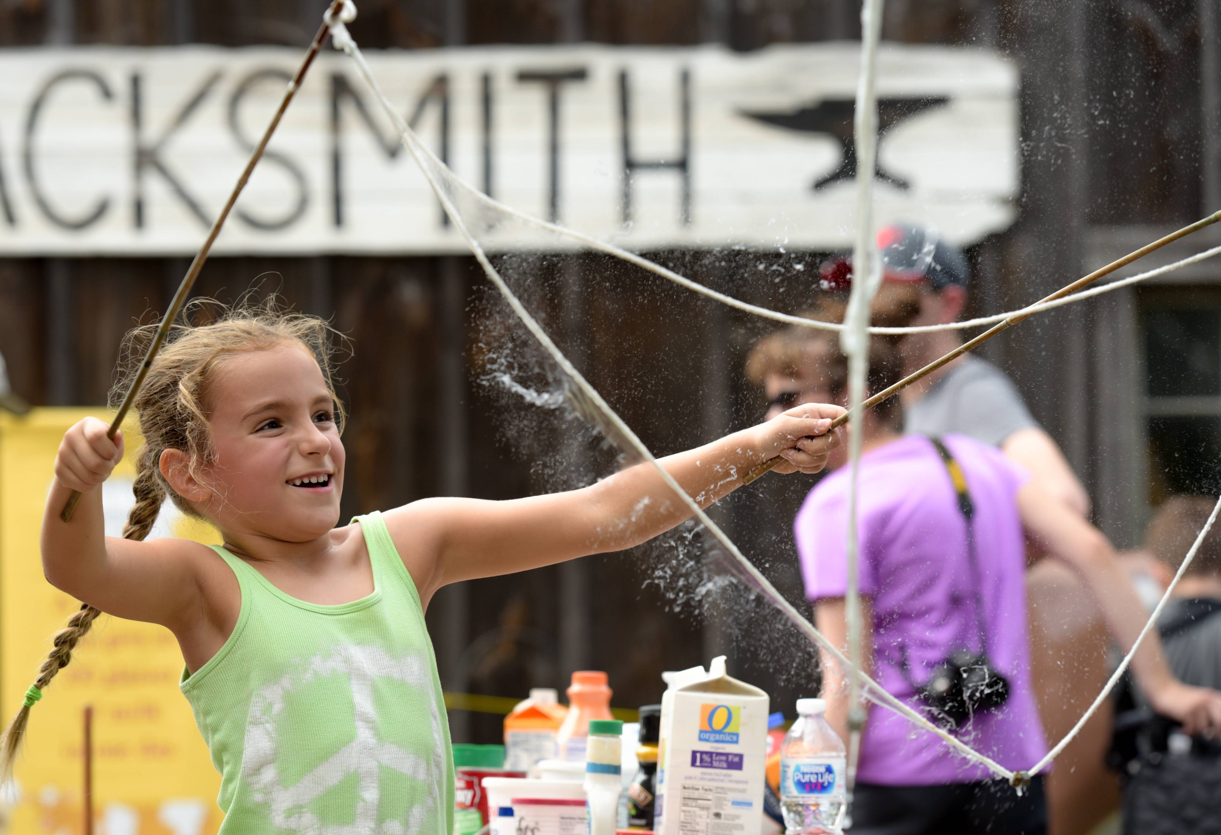 Lexie Mohr, 6, of Lisle reacts to the popping of a huge soap bubble she made Sunday with some string and two sticks at the annual Lisle Depot Days.