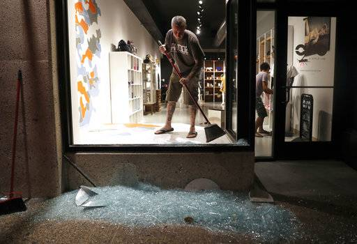 Scott McRoberts helps clean up broken glass after a violent crowd broke windows on many businesses after clashing with police Saturday, Sept. 16, 2017, in University City, Mo. Earlier, protesters marched peacefully in response to a not guilty verdict in the trial of former St. Louis police officer Jason Stockley. (AP Photo/Jeff Roberson)