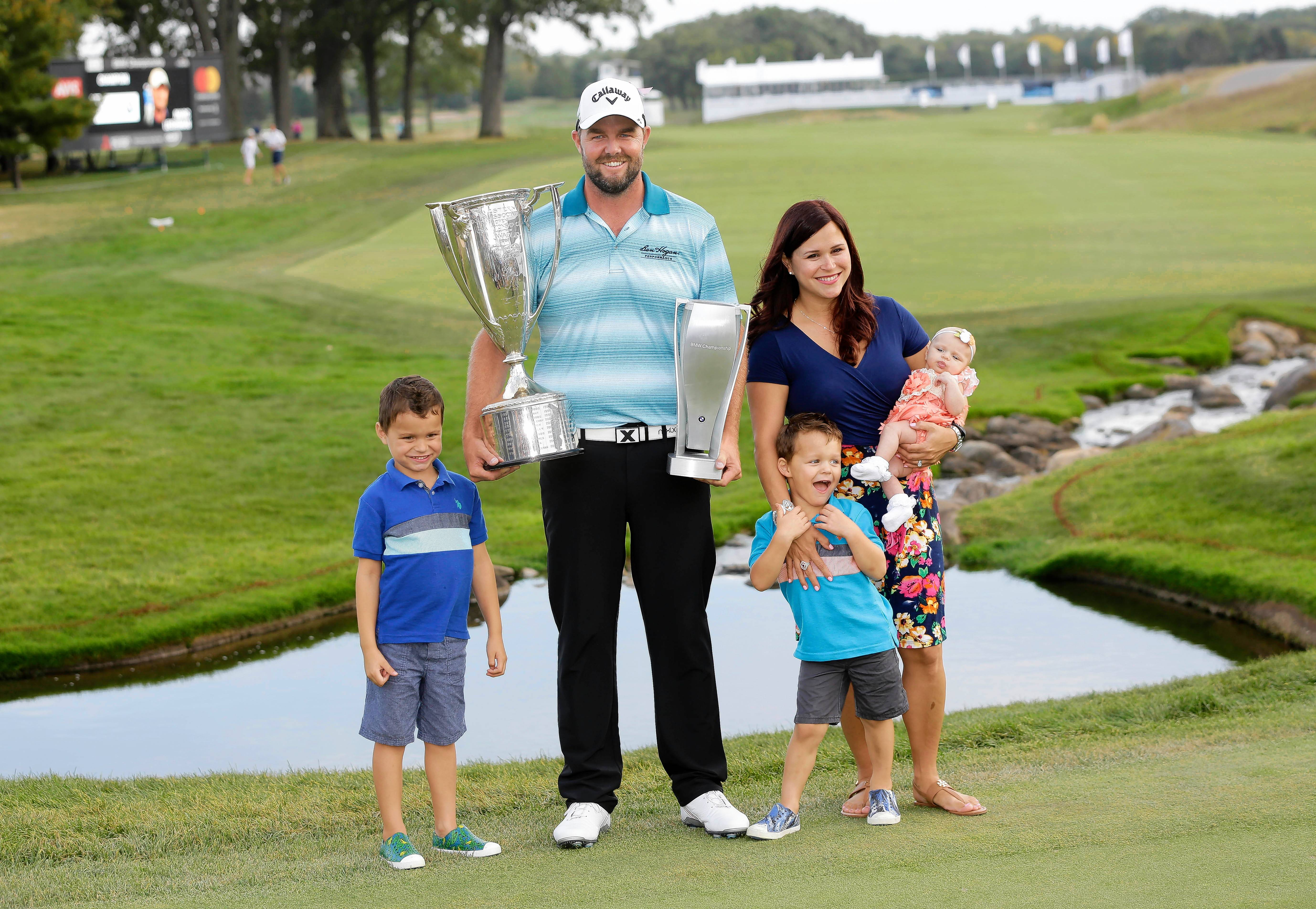 Marc Leishman, center, smiles as he poses with the Wadley Cup, left, the BMW Championship trophy and his family from left, son Harvey, son Oliver, wife Audrey and daughter Eva after winning the BMW Championship golf tournament at Conway Farms Golf Club, Sunday, Sept. 17, 2017, in Lake Forest, Ill. (AP Photo/Charles Rex Arbogast)