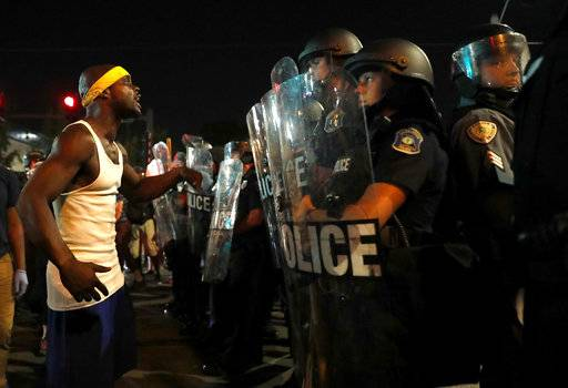 A man yells at police in riot gear just before a crowd turned violent Saturday, Sept. 16, 2017, in University City, Mo. Earlier, protesters marched peacefully in response to a not guilty verdict in the trial of former St. Louis police officer Jason Stockley. (AP Photo/Jeff Roberson)